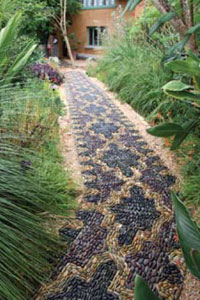 Anne's pebble mosaic footpath winds organically through a lush garden.