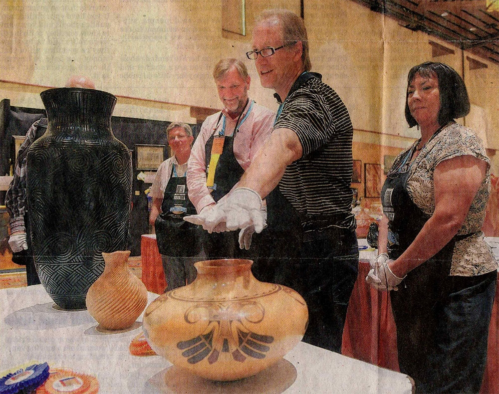 Mark Sublette shown with his hand out above a pot. Photography by Eddie Moore. Published courtesy Metro and NM Albuquerque Journal, August 22, 2009