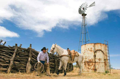 Fred and his favorite roping horse, Eagle, in front of his authentic style mesquite corral. The ranch's windmill is visible in the background. Photography by Valerie Hayken Photography and Design.