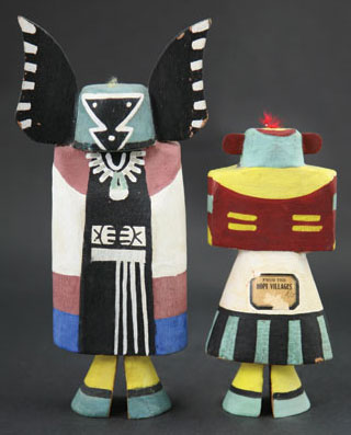 "Hopi Kachina Tourist Dolls. The kachina on the left is Angwusnasomtaqa, or Tumas Crow Mother. She wears a woman's dress and ceremonial robe with green moccasins. She appears in the Bean Dance and is considered the mother of all the kachinas by some Hopi. Her Hopi name literally means ""Man with Crow Wings Tied To."" The kachina on the right is I'she, or the Mustard Green Kachina. This kachina has a green mask with red ears, black warrior marks on the cheeks, rectangular eyes, and a triangular mouth."