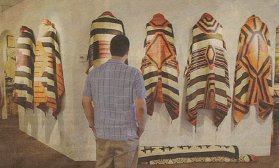 "Michigan resident Anthony Hsu looks over some of the Navajo chief blankets that were made between 1850 and 1870. About 30 rare blankets are on display at the Mark Sublette Medicine Man Gallery in ""Masterpieces of the Loom,"" a show that continues through May 20"